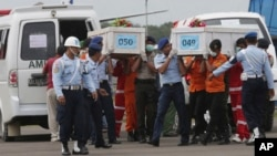 Members of the National Search and Rescue Agency carry coffins containing bodies of the victims aboard AirAsia Flight 8501 to transfer to Surabaya at the airport in Pangkalan Bun, Indonesia, Monday, Jan. 19, 2015.