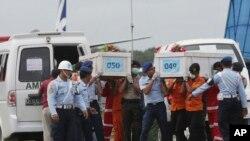 1月19日,印尼救援人員將從亞航飛機殘骸中發現的屍體手提移送上岸。