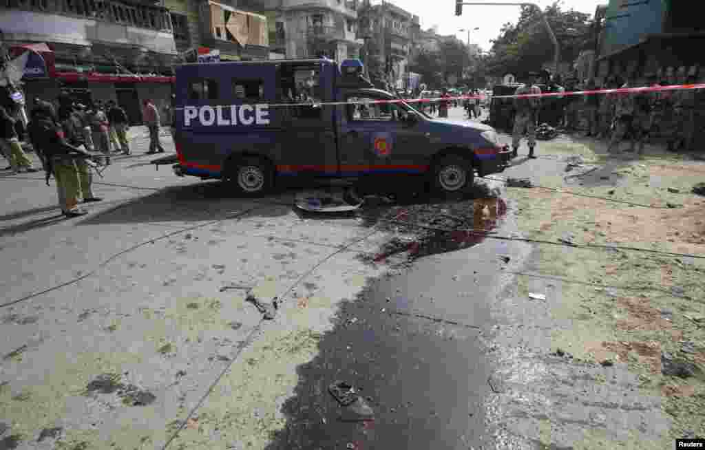 Paramilitary soldiers and police officers gather at the site of a bomb blast in Karachi, Pakistan, June 26, 2013.