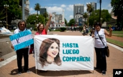 "FILE - Government supporters hold a banner that reads in Spanish ""See you soon colleague"" featuring an image of President Cristina Fernandez in Buenos Aires, Argentina, Dec. 9, 2015."