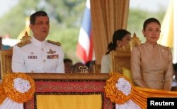 FILE - Thailand's Crown Prince Maha Vajiralongkorn (L) and Royal Consort Princess Srirasmi watch the royal plowing ceremony in Bangkok.