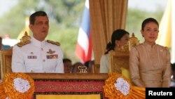 FILE - Thailand's Crown Prince Maha Vajiralongkorn (L) and Royal Consort Princess Srirasmi watch the royal plowing ceremony in Bangkok.