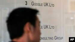 A man enters an office building with small Google UK Limited sign in London, Jan. 28, 2016.