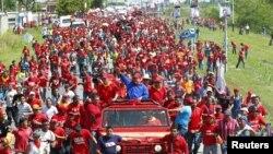 Presiden Venezuela, Hugo Chavez, melambaikan tangannya kepada para pendukung yang memadati jalanan kota Sabaneta, negara bagian Barinas (1/10).