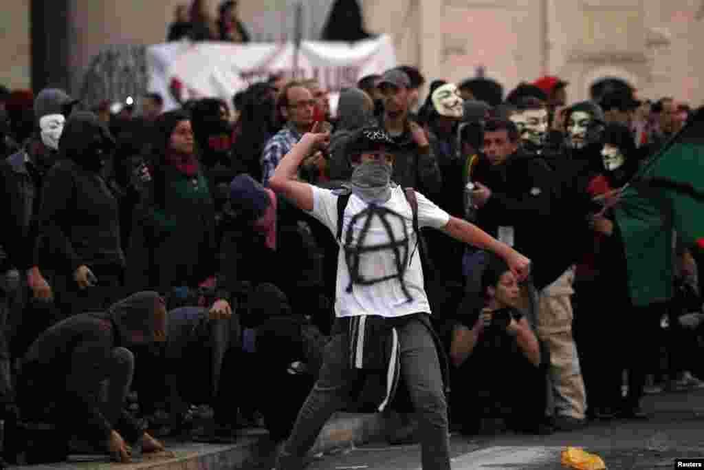 Manifestante arremessa pedras contra o cordão policial
