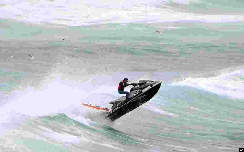 A rescuer on a jet ski battles rough seas while searching for a missing swimmer at Bondi Beach in Sydney, Australia. Police say a 22-year-old Japanese man went missing while swimming with a friend in rough surf on Nov. 4, 2013.