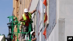 FILE - Workers build an apartment and retail complex in Nashville, Tenn., Oct. 6, 2017.