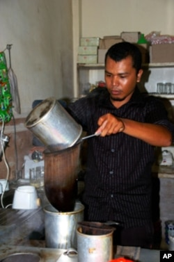 Arfian makes Coffee at his cafe after tsunami recovery program. Photo by Christoph Ernesti