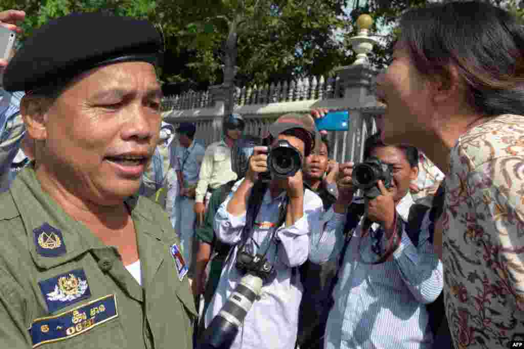 A Cambodian rights activist (R) shouts slogans (short and memorable phrases) in front of police at a protest next to the Australian embassy in Phnom Penh. Australia plans to start sending asylum-seekers to Cambodia by the end of the year and will pay the Southeast Asian nation Aus$40 million (US$35 million) to accept them.