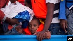 Un garçon assis dans une embarcation en bois transportant plus de 700 migrants, vers Sabratha, Libye, le 29 août 2016.
