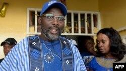George Weah didampingi istrinta Clar, berbicara kepada media di luar rumahnya di Monrovia, Liberia.