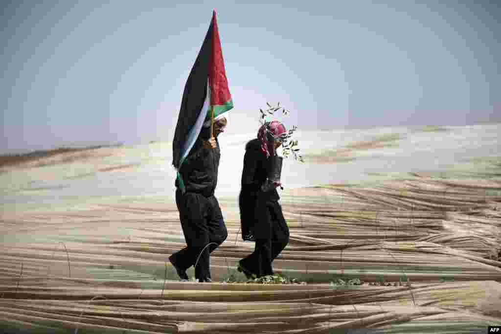 "Palestinians, a man holding a Palestinian flag and a woman carrying an olive tree, walk through rows of greenhouses on ""Land Day"" during which people notably plant olive trees near the Israeli border in Jabalia, in the northern Gaza Strip."