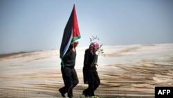 "FILE - Man holding a Palestinian flag and a woman carrying an olive tree walk through rows of greenhouses on ""Land Day,"" during which people plant olive trees near the Israeli border in Jabalia, northern Gaza, March 29, 2014."
