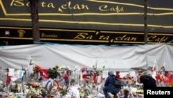 Beberapa orang terlihat berada di depan rangkaian bunga yang diletakkan oleh warga yang ikut berduka di depan Kafe Bataclan, salah satu lokasi yang menjadi sasaran serangan mematikan di Paris, Perancis, 26 November 2015 (Foto: dok).