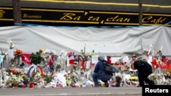 FILE - People mourn in front of the screened-off facade of the Bataclan Cafe adjoining the concert hall, one of the sites of the deadly Nov. 13 Paris attacks that killed 130 people, in Paris, France, Nov. 26, 2015.