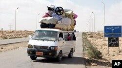 Carrinha carregada de gente e haveres a caminho da fronteira da Líbia com o Egipto