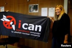 핵무기폐기국제운동(ICAN) 비어트리스 핀 사무국장이 6일 노벨평화상 수상자 발표 직후 스위스 제네바 사무실에서 깃발을 들어보이며 자축하고 있다.