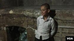 Seorang anak laki-laki Yazidi berdiri di dekat pintu masuk kuil Yazidi di Lalish, Irak.