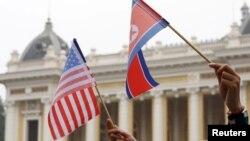Warga memegang bendera AS dan Korea Utara sambil menunggu iring-iringan mobil pemimpin Korea Utara Kim Jong Un dalam perjalanan ke Hotel Metropole untuk KTT AS-Korea Utara kedua di Hanoi, Vietnam, 28 Februari 2019. (Foto: REUTERS/Kham)