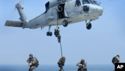 FILE - Navy SEALs training. SEALs are maritime special operations forces who strike from the sea, air and land.