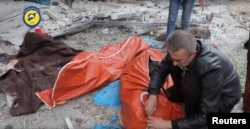 A man wraps a body in a street of rebel-held eastern Aleppo after artillery bombardment, which rescue workers say has killed at least 45 people, mostly women and children, Syria, in this still image taken on Nov. 30, 2016 from a social media website obtained by Reuters.