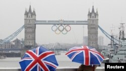 Two tourists stand under Union flag umbrellas as they take pictures from London Bridge, of Tower Bridge adorned with the Olympic rings, on a wet summer's morning in central London July 6, 2012.