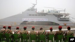 Members of Iran's Revolutionary Guard sit in front of a newly inaugurated high-speed catamaran, in the port city of Bushehr, northern Persian Gulf, Iran, Sept. 13, 2016.