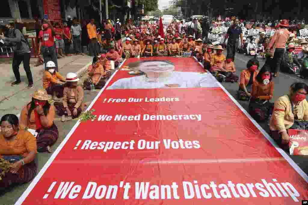 Myanma - Mandalay şəhərində nümayişçilər üzərində həbsdə olan lider Aung San Suu Çinin şəkli olan nəhəng plakatın qarşısında oturaraq çevriliş əleyhinə etiraz aksiyası keçirir.