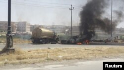 Vehículos del ejército iraquí arden tras los combates entre islamistas y fuerzas gubernamentales.