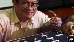 Filipino archeologist Armand Salvador Mijares shows bones and teeth they recovered from Callao Cave belonging to a new specie they called Homo luzonensis during a press conference in metropolitan Manila, Philippines on Thursday, April 11, 2019. (AP Photo/