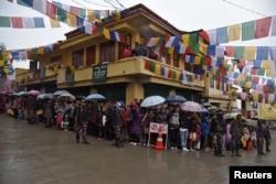FILE - People stand in rain as they wait to welcome Tibetan spiritual leader Dalai Lama in Bomdila in the northeastern state of Arunachal Pradesh, India, April 4, 2017.