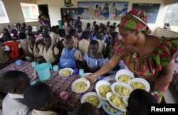 """FILE - Students wait to eat at a school canteen, near a sign on the wall that reads """"Eating well to learn better,"""" in N'zikro, Aboisso, Ivory Coast, Oct. 27, 2015."""