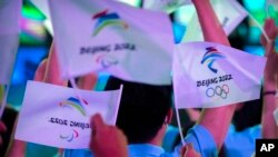 FILE - Participants wave flags with the logos of 2022 Beijing Winter Olympics and Paralympics before a launch ceremony to reveal the motto for the Winter Olympics and Paralympics in Beijing, Sept. 17, 2021.
