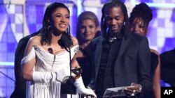 "Cardi B, left, accepts the award for best rap album for ""Invasion of Privacy"" as Offset looks on at the 61st annual Grammy Awards, Feb. 10, 2019, in Los Angeles."