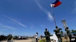 2015年5月11日,一个菲律宾居民和菲律宾军人一起在南中国海的斯普拉特利群岛(南沙群岛中的派格阿萨岛(中业岛)举行升旗仪式。(资料照片)