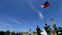 2015年5月11日,一個菲律賓居民(中)和菲律賓軍人一起在南中國海的斯普拉特利群島(南沙群島中的派格阿薩島(中業島)舉行升旗儀式。(資料照片)