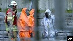 Bomberos y personal de emergencia con trajes especiales revisan el consulado de Estados Unidos en Berlin, Alemania, donde se dio una falsa alarma por la presencia de alguna sustancia o gas sospechosos.
