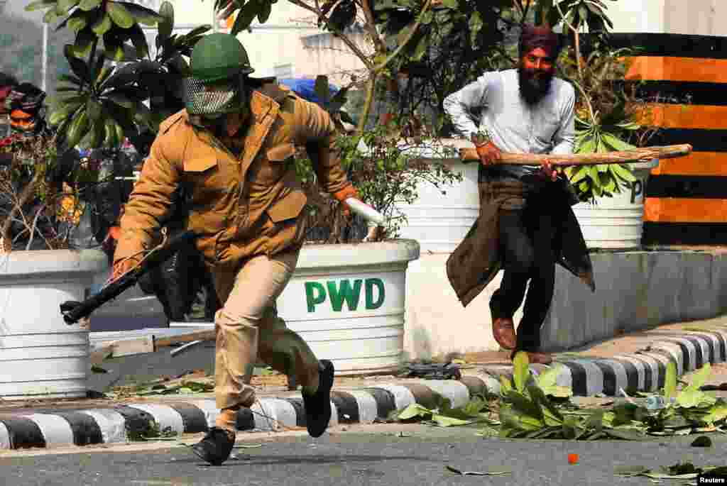 A farmer chases a police officer during a protest in New Delhi against farm laws introduced by India's government.