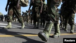 FILE - Members of the Eastern Africa Standby Brigade from Uganda march to board a French tactical aircraft C160 Transall at the French Air Base 188 in Djibouti, Dec. 5, 2009.