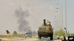 Anti-Gaddafi forces' armored personnel carrier advances to the front line at Teassain area, 90 km (56 miles) east of Sirte, amid heavy shelling by pro-Gaddafi forces, September 9, 2011.