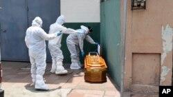 Agents de santé retirant un cercueil avec un corps laissé à l'extérieur d'une maison à Guayaquil pendant la pandémie de Covid-19, Équateur, 6 avril 2020. (Photo AP/Edison Choco)