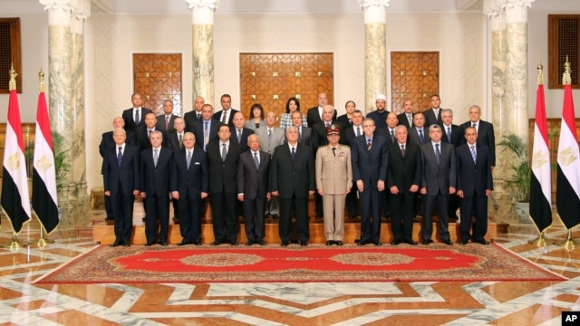 This image released by the Egyptian Presidency on July 16, 2013 shows interim President Adly Mansour, center, with his new cabinet ministers at the presidential palace in Cairo, Egypt.