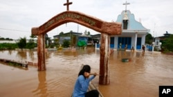A Cambodian woman pushes a church gate with an oar to steer her wooden boat in a flooded area along the Mekong river in Koh Phos village, Kandal province near Phnom Penh, Cambodia, Sunday, Sept. 29, 2013. (AP Photo/Heng Sinith)