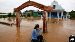 A Cambodian woman pushes a church gate with an oar to steer her wooden boat in a flooded area along the Mekong river in Koh Phos village, Kandal province near Phnom Penh, Cambodia, Sunday, Sept. 29, 2013.