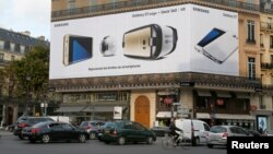 FILE - An advertisement board place de l'Opera displays a Samsung Galaxy S7 edge mobile phone, a gear VR virtual reality headset and a 360 VR Camera in Paris, France, Oct. 26, 2016.