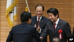 Hwang Woo-yea (tengah), ketua partai berkuasa di Korea Selatan, Saenuri dan kepala parlemen Korea Selatan, bertepuk tangan saat PM Jepang Shinzo Abe (kanan) berjabat tangan dengan seorang anggota parlemen Korea Selatan seusai memberikan sambutan dalam pembukaan sidang parlemen ke-36 parlemen Jepang-Korea Selatan di Tokyo, Jumat (29/11).