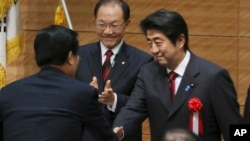 아베 신조 일본 총리(오른쪽)가 29일 도쿄에서 열린 한·일 의원연맹 합동총회에서 한국 국회의원들과 인사를 나누고 있다.