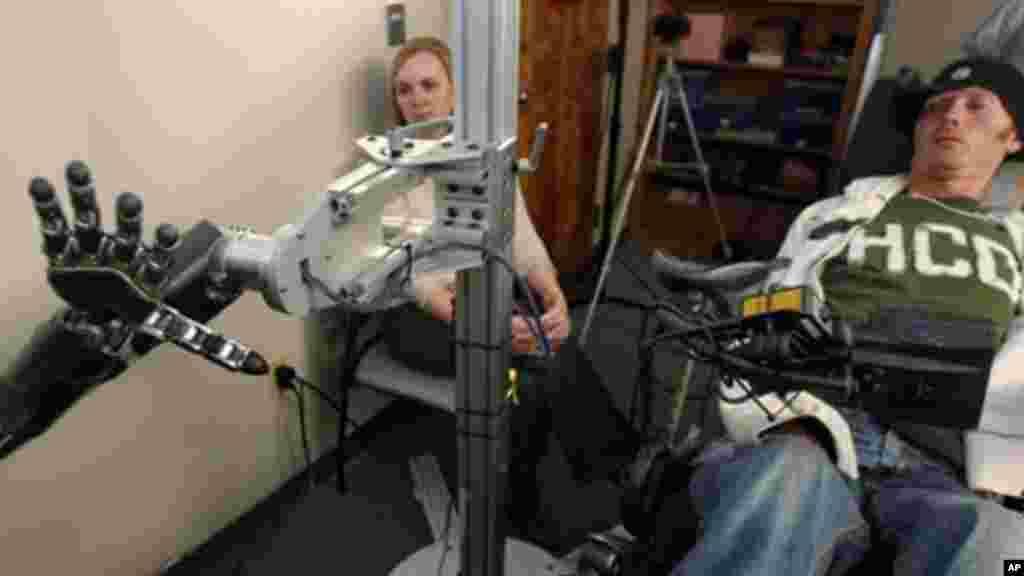 Sur cette photo prise mercredi le 21 septembre 2011, le professeur assistant Jennifer Collinger, à gauche, observe comment un sujet de recherche tétraplégique, Time Hemmes, dirige la prothèse mécanique de la main lors d'une session d'essais au centre médical de la faculté l'université de Pittsburgh. (AP Photo/Keith Srakocic)