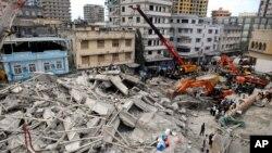 Regu penyelamat menggunakan mesin penggali untuk memindahkan reruntuhan gedung dari bangunan yang ambruk di pusat kota Dar es Salaam, Tanzania (29/3).