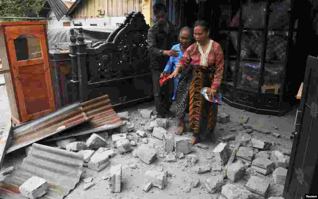 Residents leave their house after it was hit by a strong earthquake in Bener Meriah district in Central Aceh, July 2, 2013.